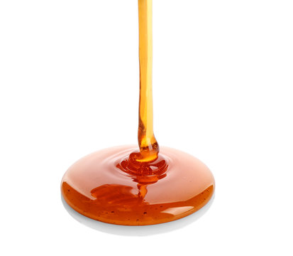 Sweet honey pouring on white background