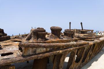 Schiffswrack mit Touristen im Hintergrund am Strand