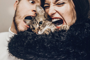 happy stylish hipster family hugging with their cat. man and woman holding kitty and having fun and taking selfie, happy family moments