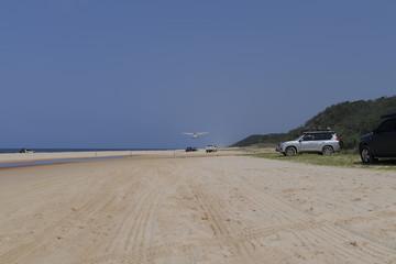 Landeanflug eines Sportflugzeuges auf einer Sandpiste am Strand