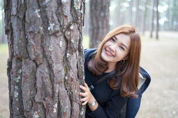 Beautiful asian woman with brown hair hiding behind pine tree