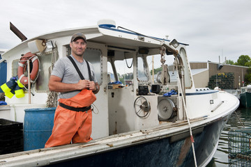 Portrait of proud lobsterman standing on his docked boat
