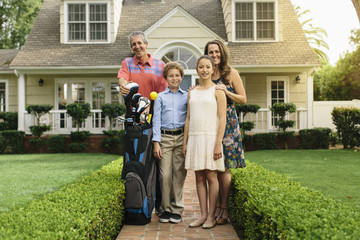 A jovial middle age man accompanies by his young boy, teenage daughter and middle age wife stands with his golf kit.