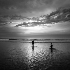 A father and son wade into the Pacific Ocean while vacationing at Rockaway Beach, Oregon.