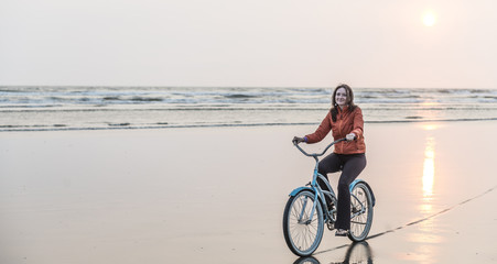 A woman rides a bike on the beach at sunset in Washington State.