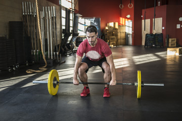A man lifts weights at a cross fit gym.