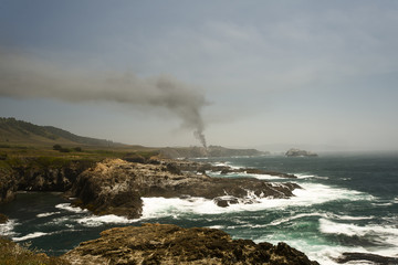 Smoke from a distant fire is seen along a cliff-lined coastline.