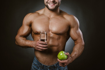 Bodybuilder with an apple and a glass of water
