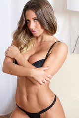 Sexy lingerie fitness woman in black showing muscular body