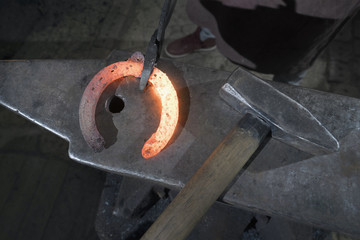 Apprentice blacksmith hammering red hot horseshoe on anvil at workshop