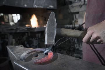 Apprentice blacksmith hammering red hot horseshoe on anvil at workshop