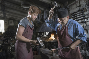 Blacksmith and apprentice hammering red hot iron bar at workshop