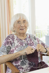 Senior woman crocheting in rest home