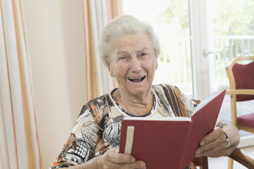Portrait of happy senior woman reading book in rest home