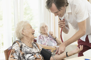Caregiver checking blood pressure of senior woman in rest home