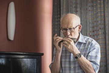 Senior man  blowing a harmonica instrument