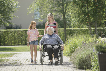 Senior woman on wheelchair with daughter and granddaughter at rest home park