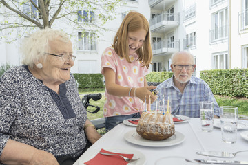 Family celebrating birthday of grandmother in rest home yard