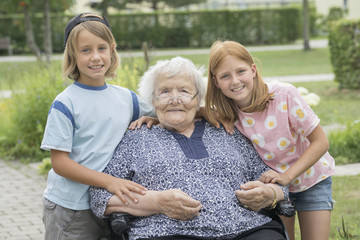 Senior woman on wheelchair with grandchildren at rest home park