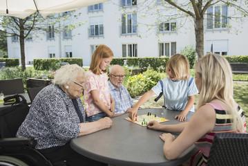 Multi-generation family playing board game at nursing home
