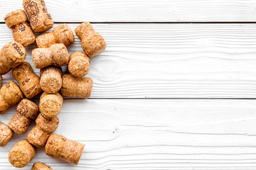 Heap of wine bottle corks on white wooden background top view copyspace