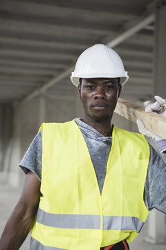 Portrait of construction worker carrying wooden plank at building site