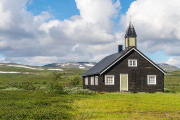 Wooden church on a green meadow on a background of a cloudy sky,
