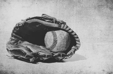 Vintage style grunge image of baseball in glove, shows sport equipment for game.  Ball caught in mitt in black and white.