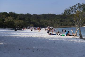 Touristen am Sandstrand eines Badesee mit Wald im Hintergrund