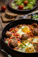 shakshuka, the Israeli dish of eggs, tomatoes and meatballs with greens on wooden background