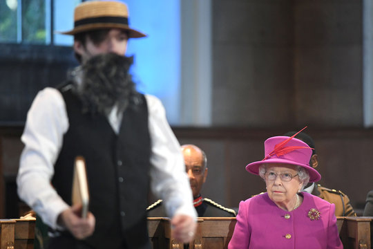 Britain's Queen Elizabeth watches a performance by the Artless Theatre Company during the Scripture Union's 150th anniversary service of celebration at St Mary's Church, in London