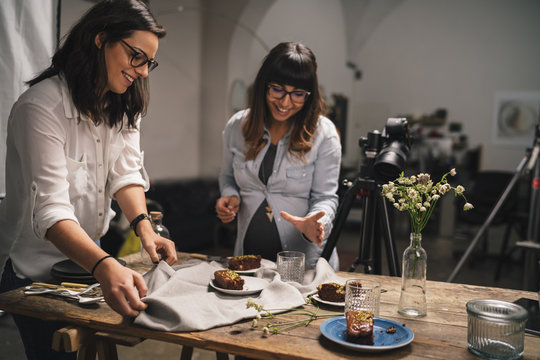Pregnant woman with a colleague working on a food photoshoot in a studio