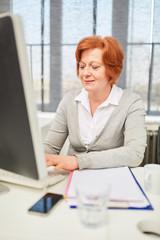 Ältere Frau als Schreibkraft am Computer