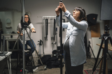 Pregnant woman working in a photographic studio