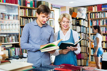 Smiling young man and mature woman holding books