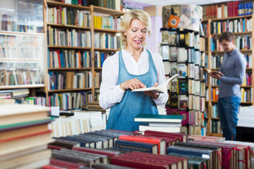 Positive mature woman reading open book