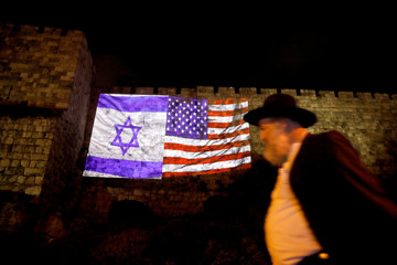 Man walks by as the Israeli national flag and an American one are projected on a part of the walls surrounding Jerusalem's Old City