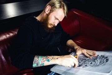 Male artist with tattoo on her hand in a dark room draws a picture with crayons while sitting on the couch
