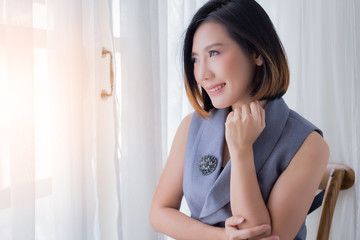 smart asian woman in working dress in thinking somthing next to white curtain wndow