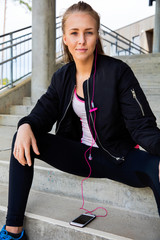Woman In Sportswear Listening Music On Mobile Phone At Stairway