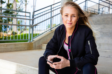 Young Woman In Sportswear Listening Music On Mobile Phone