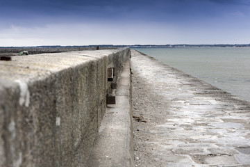 Long concrete straight dam in low tide in france