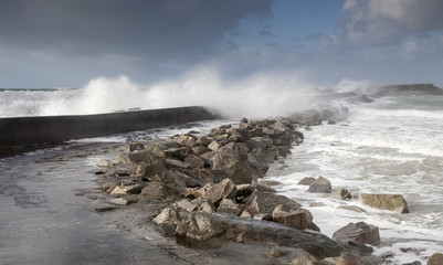 furious strong stormy waves near a concrete dam coastline in France