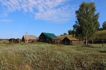 Wall Mural - Very old wooden houses in the remote Russian village in the summer against a blue sky