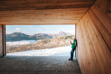 Man drinks a hot drink in wooden hangar with mountains panorama view