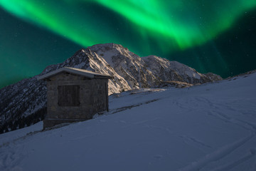 aurora borealis above the mountains with a cottage in the foreground