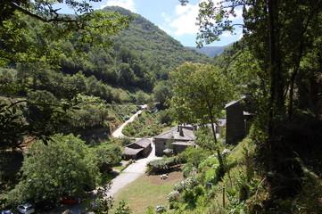 Cabañas de piedra entre montes verdes bajo cielo azul . Cabins among green mountains under blue sky