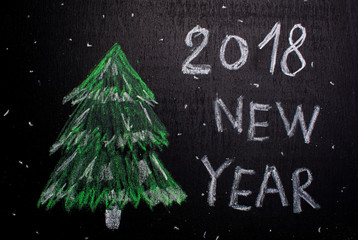 Christmas tree silhouette chalked on a blackboard. The inscription on the right is 2018 new year.  Minimalism concept.