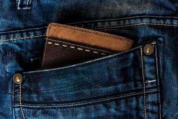 Leather wallet in a blue jeans pocket.
