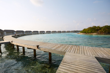 Water bungalows in hotel on Maldives. Villas on Indian ocean at luxury spa resort.